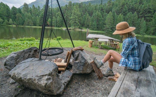 Frau sitzt an Feuerstelle in der Schweiz