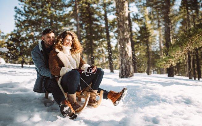 Schlitteln in der Schweiz: Paar auf dem Schlitten