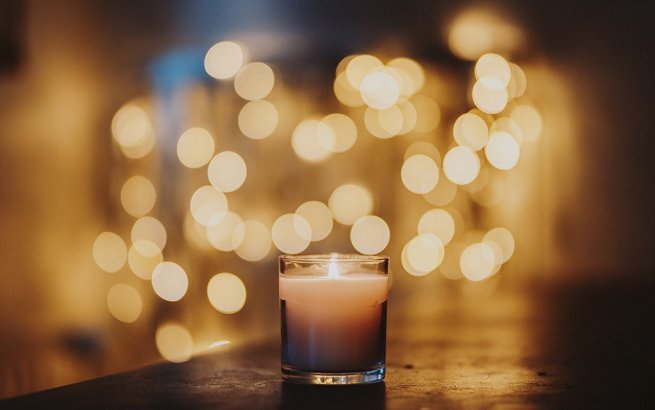 Kerze mit Lichtern im Hintergrund